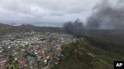 Asap membubung dari pesawat marinir Osprey setelah mendarat secara darurat di Markas Angkatan Udara Bellows, dekat Waimanalo. Hawaii (17/5). (AP/Brandon Kelly)