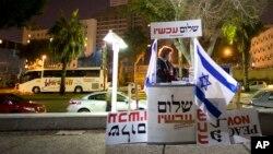 تل ابیب میں امن کی حامی ایک سرگرم کارکن احتجاج سے قبل پلے کارڈ رکھ رہی ہے۔ (فائل فوٹو)