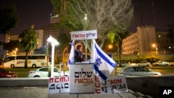 FILE - An Israeli peace activist hands out signs prior to a protest in Tel Aviv, Israel, Jan. 15, 2011. A newly-proposed Israeli law would require nonprofit groups to disclose foreign sources of funding.