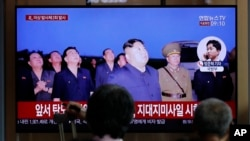 People watch a TV news program reporting about North Korea's firing projectiles with a file image of North Korean leader Kim Jong Un at the Seoul Railway Station in Seoul, South Korea, Friday, Aug. 16, 2019.