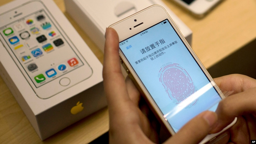 In this Sept. 20, 2013 file photo, a customer configures the fingerprint scanner technology built into the Apple iPhone 5S at an Apple store in Wangfujing shopping district in Beijing, China. (AP Photo/Andy Wong, File)