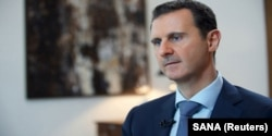 FILE - Syria's President Bashar al-Assad speaks during an interview with the Iranian Khabar TV channel in this handout photograph released by Syria's national news agency SANA, Oct. 4, 2015.
