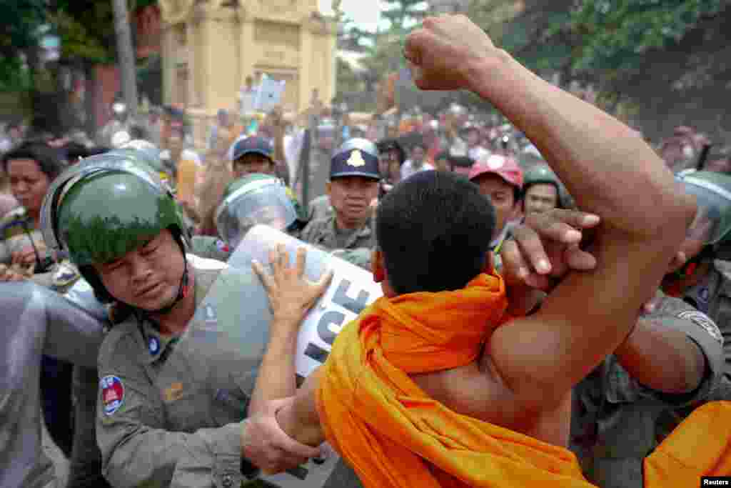 Riot policemen protect a man accused of trying to hit a Buddhist monk, during protests against alleged election irregularities in Phnom Penh July 28, 2013.