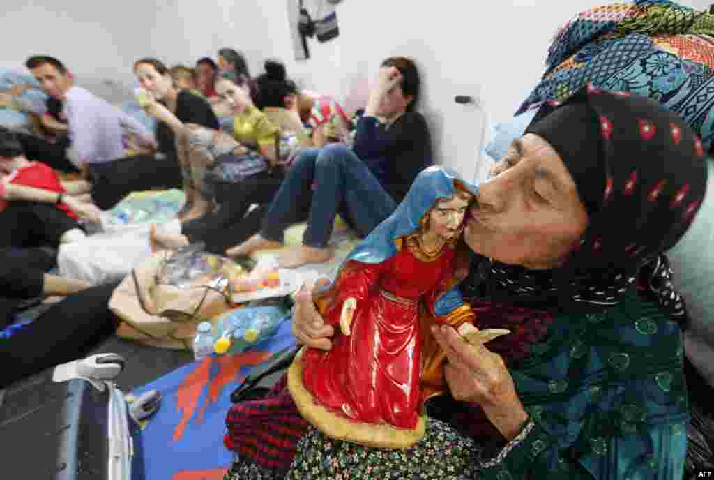 An Iraqi Christian woman fleeing the violence in the village of Qaraqush and Bartala kisses the head of a statue representing a Christian saint at a community center in the Kurdish city of Arbil in Iraq's autonomous Kurdistan region.