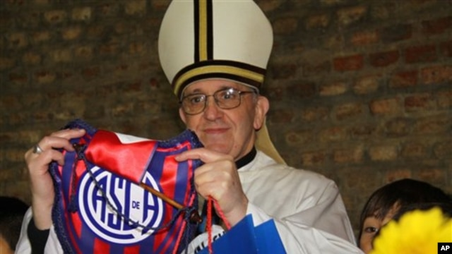 In this March 24, 2011 image released by the San Lorenzo de Almagro soccer team on March 13, 2013, Argentina's Cardinal Jorge Bergoglio holds up a small flag of the San Lorenzo soccer team in Buenos Aires, Argentina.