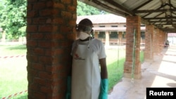 A health worker prepares to takes off protective clothing after visiting the isolation ward at Bikoro hospital, which received a new suspected Ebola case, in Bikoro, Democratic Republic of Congo, May 12, 2018.