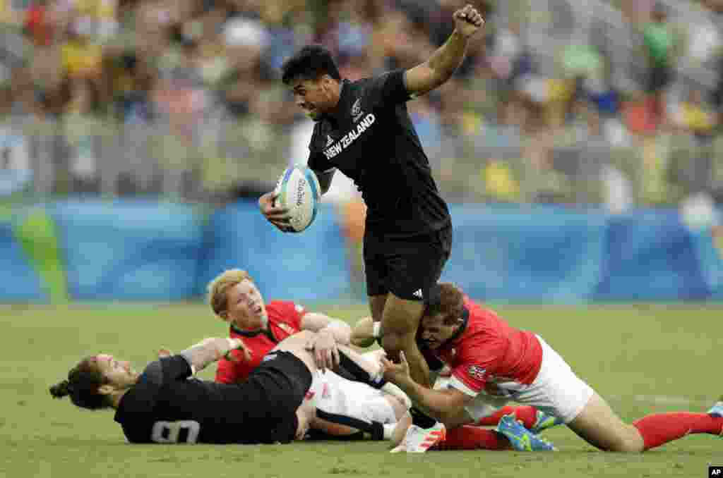 New Zealand's Regan Ware, top, is tackled by Britain's players during the men's rugby sevens match at the Summer Olympics in Rio de Janeiro, Brazil, Wednesday, Aug. 10, 2016.