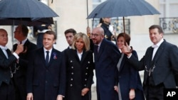 Belgian Prime Minister Charles Michel, center, and his partner Amelie Derbaudrenghien, second right, are greeted by French President Emmanuel Macron, left, and his wife Brigitte Macron as they arrive at the Elysee Palace in Paris to participate in a World