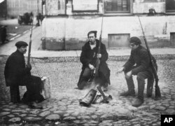 In this photo taken in Oct. 1917, provided by Russian State Archive of Social and Political History, armed revolution workers warm themselves at a bonfire in St.Petersburg, Russia. From left: Ivanov, Yarosh and Gribovsky.