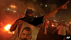 A Supporter of ousted President Mohammed Morsi holds a poster of him during clashes in downtown Cairo, Egypt. July 15, 2013.