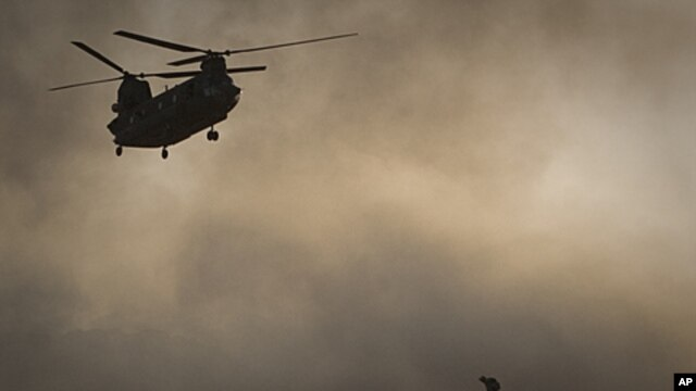A US Marine tries to shelter from the dust as a Chinook helicopter arrives to pick up supplies at Forward Operating Base Edi in the Helmand Province of southern Afghanistan,June 9, 2011 file photo