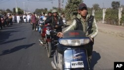 Indian journalists walk with their two wheelers at the funeral procession of fellow journalist Bwizamani Singh in Imphal, India, Tuesday, Dec. 25, 2012.