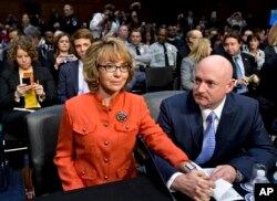 FILE - Former U.S. Rep. Gabrielle Giffords, who survived a gunshot to the head in 2011 during a mass shooting in Tucson, Ariz., sits with her husband, retired astronaut Mark Kelly, at a Senate panel hearing on gun violence, on Capitol Hill in Washington.