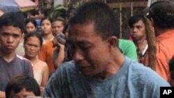 圖中的這名父親抱著孩子的屍體。這名兒童是週末在菲律賓南部的颱風襲擊中死亡