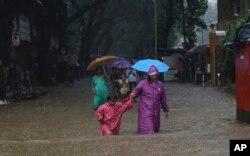 بارشوں سے متاثرہ افراد محفوظ مقامات کی طرف جا رہے ہیں۔ 2 جولائی 2019