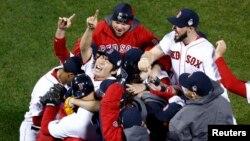 El lanzador relevista Koji Uehara, de los Medias Rojas de Boston, celebra junto a sus compañeros el último out que les dió el título de la Serie Mundial en el Fenway Park