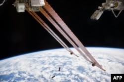 In the grasp of the Japanese robotic arm, the CubeSat deployer (upper right) releases a pair of NanoRacks CubeSat miniature satellites (bottom center) in this NASA image obtained August 27, 2014.