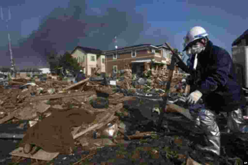 A body, covered in a blanket, lies in the rubble of a destroyed neighborhood as firefighters search the area in Sendai, Miyagi Prefecture, northeastern Japan, two days after a giant quake and tsunami struck the country's northeastern coast, March 13, 2011