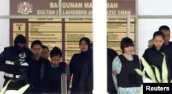 FILE - Vietnamese Doan Thi Huong and Indonesian Siti Aisyah who are on trial for the killing of Kim Jong Nam, the estranged half-brother of North Korea's leader, are escorted as they leave the Shah Alam High Court on the outskirts of Kuala Lumpur, Malaysia.