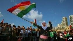 یک زن کرد که از جنگ در سوریه گریخته، در بیروت در جشن نوروز با پرچم کردستان.