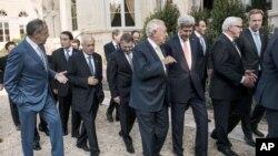 """在合影后,俄罗斯外长(左)与阿拉伯联盟秘书长阿拉比(左二)交谈;西班牙外长加西亚-马加略(中)跟美国国务卿克里谈话。各国外长在巴黎出席有关打击""""伊斯兰国""""的会议。(2014年9月15日)"""