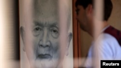 "A tourist looks at a portrait of former Khmer Rouge leader ""Brother Number two"" Nuon Chea at the Tuol Sleng Genocide Museum in Phnom Penh August 2, 2014."
