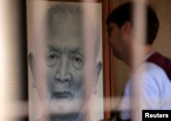 "FILE - A tourist looks at a portrait of former Khmer Rouge leader ""Brother Number two"" Nuon Chea at the Tuol Sleng Genocide Museum in Phnom Penh August 2, 2014."