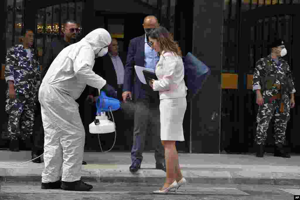 A medical worker puts disinfectant spray on Minister of Information Manal Abdul-Samad as she arrives for a parliament meeting, in Beirut, Lebanon.