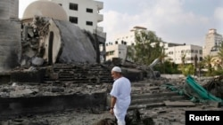 A Palestinian man looks at a mosque in Gaza City which police said was hit in an Israeli air strike.