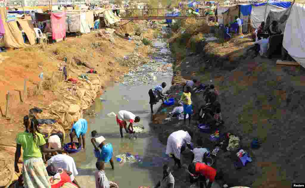 Displaced people wash their clothes in a drainage canal at Tomping camp, near Juba, Jan. 7, 2014.