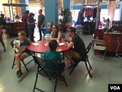 A family eats lunch and participates in the Caribbean Marketplace Trivia game in Little Haiti, Miami, Florida. (Photo: S. Lemaire / VOA)