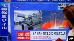 一名女士走过日本东京的一个正播放朝鲜试射导弹的新闻电视(2017年8月29日)