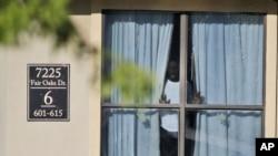 Una persona mira por la ventana del apartamento donde vivió Thomas Eric Duncan, el epicentro del brote de ébola en Dallas.