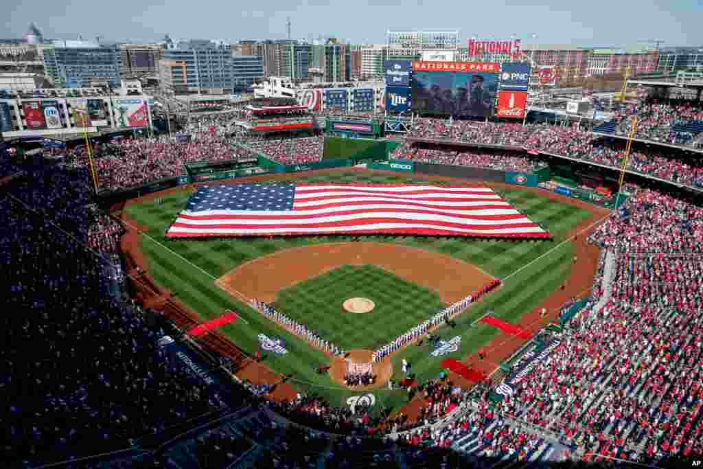 A large American flag is unfurled on the field before a baseball game between the Washington Nationals and the New York Mets on opening day at at Nationals Park in Washington, D.C., April 6, 2015.
