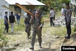 Kapolda Sulawesi Tengah Irjen Pol Abdul Rakhman Baso memikul balok kayu yang akan digunakan dalam pembangunan kembali rumah warga yang sebelumnya dibakar kelompok teroris MIT, Kamis , 3 Desember 2020. (Foto : Humas Polda Polda Sulawesi Tengah)