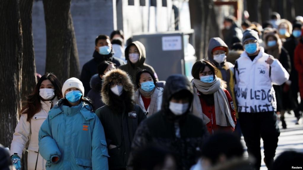 身穿厚保暖外衣的人群走过北京南锣鼓巷。(2021年1月16日)