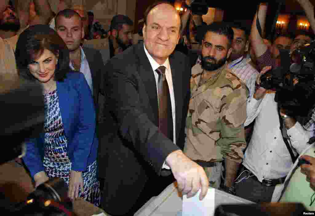 Syria's presidential candidate Hassan al-Nouri accompanied by his wife Hazar casts his vote at polling centrer in Damascus, June 3, 2014.
