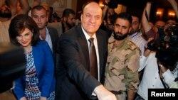 Ứng cử viên tổng thống Hassan al-Nouri và vợ đi bỏ phiếu tại Damascus, ngày 3/6/2014.