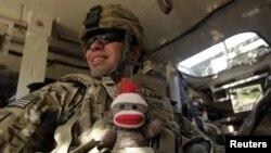 El soldado de EE.UU Moisés Ochoa del 2do Batallón de Infantería, lleva en su chaleco camuflado, a prueba de balas, un juguete de peluche para su hijo de nueve meses. El militar viaja a bordo de un vehículo blindado en la provincia de Kandahar, Afganistán.Foto: Reuters