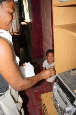 A mother cooks while her child screams for attention in a home in South Africa's Western Cape, which has one of the highest rates of Fetal Alcohol Syndrome in the world