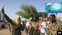 Sudanese demonstrators take a selfie during a rally outside the army headquarters in the Sudanese capital Khartoum on April 13, 2019.