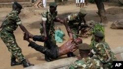 Des soldats soulèvent un blessé présumé membre de la milice Imbonerakure attaqué par des manifestants opposés au troisième mandat du président Pierre Nkurunziza, jeudi 7 mai 2015 à Bujumbura, Burundi.