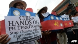 Filipino students hold replicas of Chinese maritime surveillance ships as they shout anti-Chinese slogans during a rally near Malacanang Palace in Manila on March 3, 2016, to denounce reported Chinese vessels dropping anchor near a South China Sea atoll a