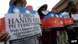 Các sinh viên Philippines cầm mô hình tàu hải giám của Trung Quốc và hô khẩu hiệu chống Trung Quốc trong một cuộc biểu tình gần Malacanang Palace ở Manila, ngày 3 tháng 3 năm 2016.