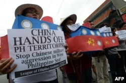 FILE - Filipino students hold replicas of Chinese maritime surveillance ships as they shout anti-Chinese slogans during a rally near Malacanang Palace in Manila, March 3, 2016.