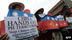 Filipino students hold replicas of Chinese maritime surveillance ships during a rally near Malacanang Palace in Manila, March 3, 2016, to denounce reported Chinese vessels dropping anchor near a South China Sea atoll claimed by the Philippines.