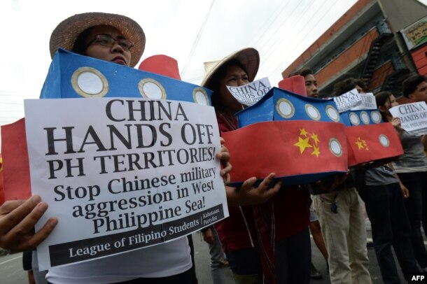 FILE - Filipino student activists hold mock Chinese ships to protest recent island-building and alleged militarization by China off the disputed Spratlys group of islands in the South China Sea, during a rally in Manila, Philippines, March 3, 2016.