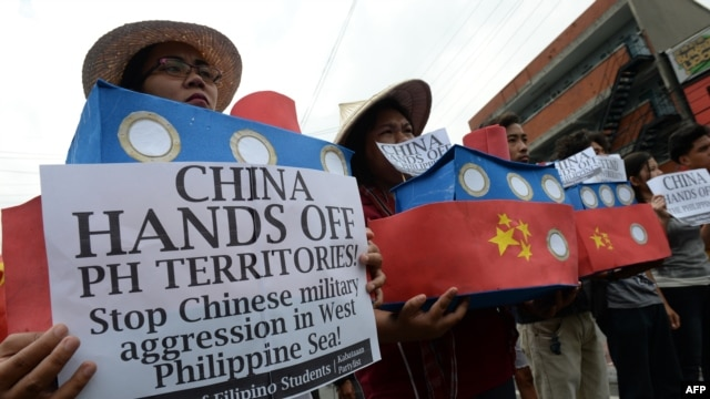 FILE - Filipino students hold replicas of Chinese maritime surveillance ships as they shout anti-Chinese slogans during a rally in Manila March 3, 2016, to denounce reported Chinese vessels dropping anchor near a South China Sea atoll.