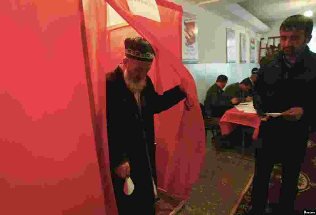 A man walks out of a voting booth at a polling station during the presidential election in Dushanbe, Nov. 6, 2013.
