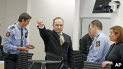 Anders Behring Breivik clenches his fist as he arrives in the courtroom for the first day of his trial in Oslo, Norway, April 16, 2012.